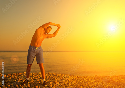 athlete practicing, playing sports and yoga on the beach at suns