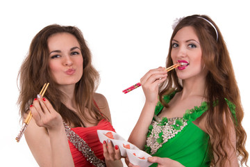 Girls with chopsticks eating sushi ginger