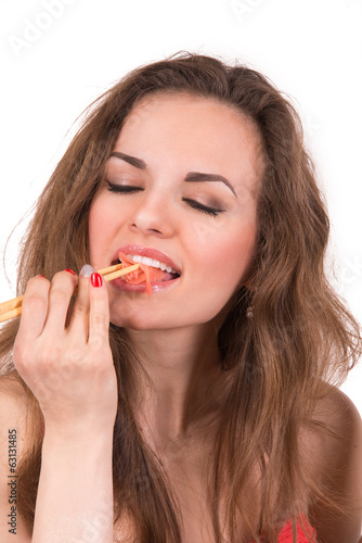 Girl with chopsticks eating sushi ginger