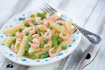 Penne pasta with shrimps and vegetables, wooden background