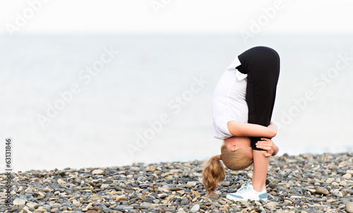 woman doing yoga and sport exercises on  beach