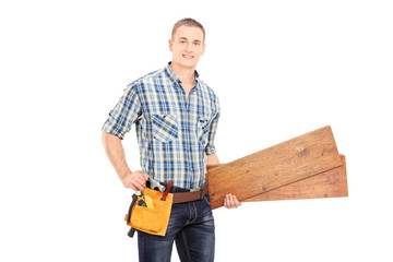 Male carpenter holding a couple of planks