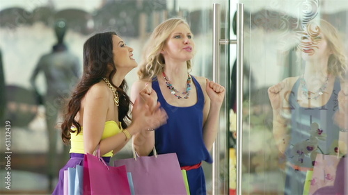 Girls discussing new collection by the shopping  window