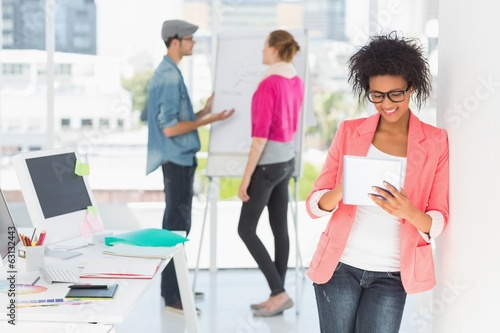 Artist using digital tablet with colleagues in at office
