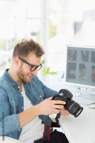 Handsome photographer holding his camera and smiling