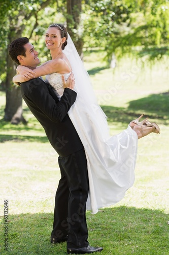 Side view groom lifting bride in garden