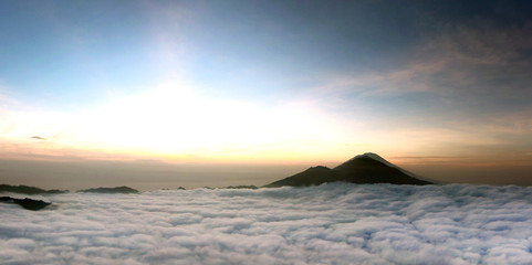 Sunrise above clouds with a mountain volcano view