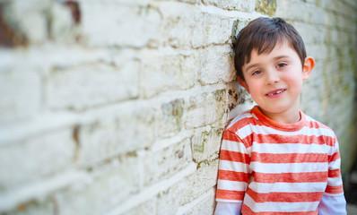 Cute happy boy leaning against brick wall