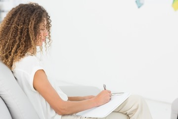Therapist taking notes on clipboard sitting on couch