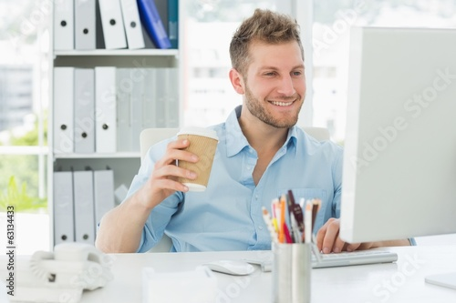 Smiling man working at his desk drinking a take away coffee