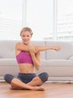 Happy blonde sitting in lotus pose stretching arms