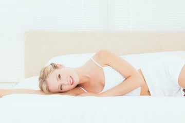 Pretty blonde lying on her bed smiling at camera
