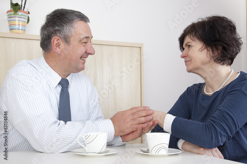 Man comforting woman over a cup coffee