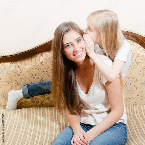 two sisters at home sharing secrets