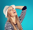 Laughing fashion girl thinking of summer holiday over blue