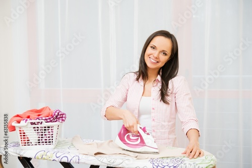 Young cheerful woman ironing clothes in home interior