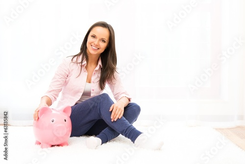 Cheerful young woman sitting on a carpet with piggybank