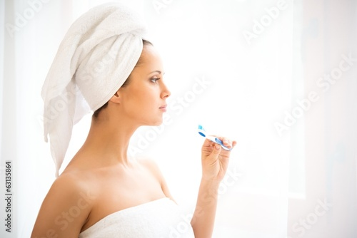 Young woman with towel on her head using toothbrush