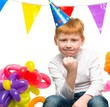 Funny little redhead boy among birthday balloons