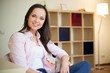 Cheerful young brunette woman in home interior