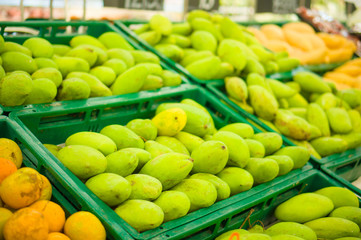 Bunch of green and yellow mango fruits on plastic boxes in store