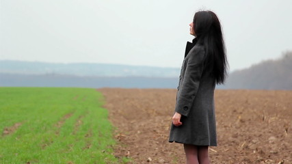 girl in a field looking thoughtfully into the distance,