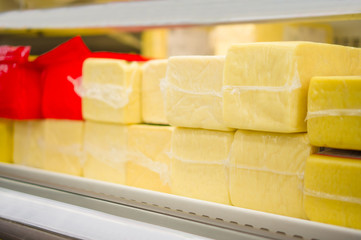 Huge brick form pieces of cheese in color packs on shelves in su