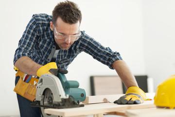 Focus carpenter sawing wood board