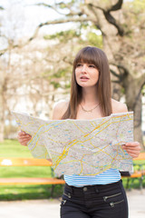 Confused young woman holding map in park