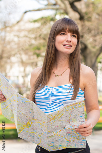 Young long haired woman holding map in park