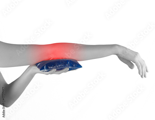 Holding ice gel pack on elbow. Medical concept photo.
