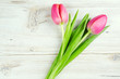 two pink tulips on white wooden surface