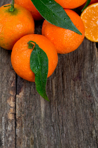 Tangerines with leaves on wooden table