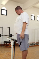 man with overweight on scales in gym
