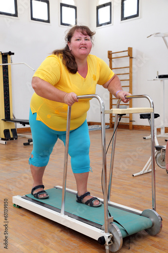 overweight woman running on trainer treadmill
