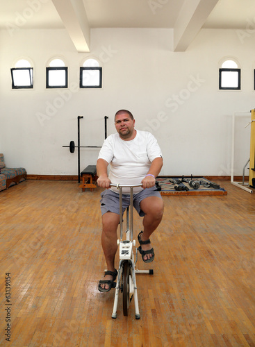 overweight man on bike simulator