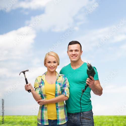 smiling couple with hammer and drill