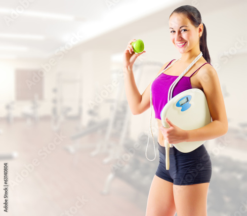 Young woman with apple and scales at gym club