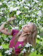 young attractive woman standing near the blossoming apple tree..