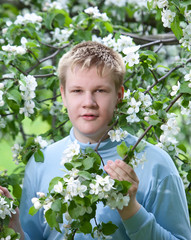 Young man, teenager standing near the blossoming apple tree...