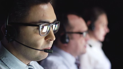 Male operator consulting clients online in working environment