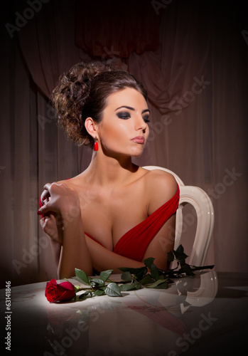 Young woman with rose flower sit on chair