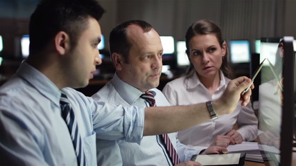 Three white-collar workers discussing computer project in office
