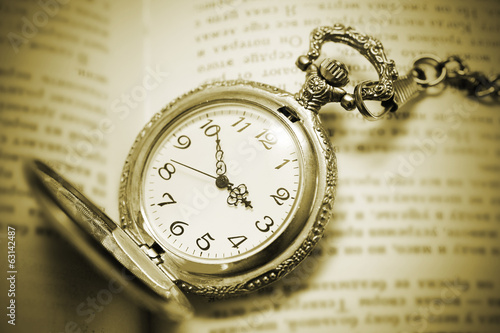 Retro vintage pocket watch lying on the book, retro style