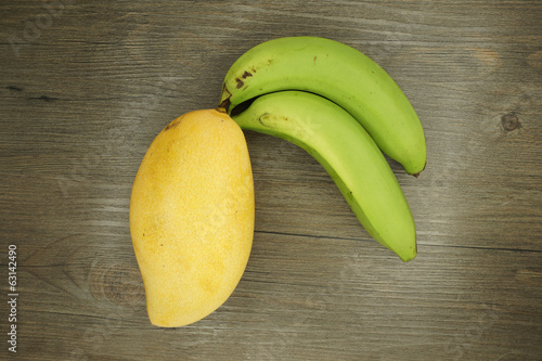 Mango or Mangifera indica and banana on wood background
