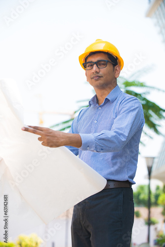 indian male architect holding plans with construction background