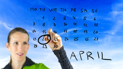 Woman marking Earth Day on a calendar