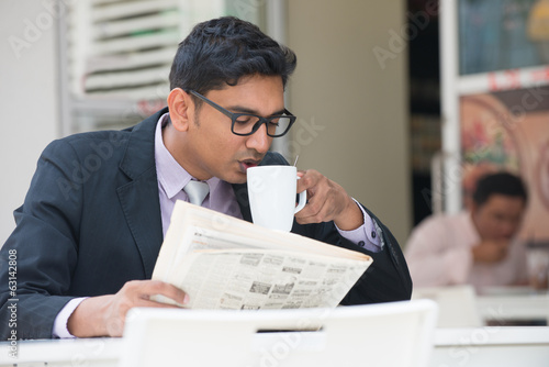 young indian business man on laptop and coffee at a cafe
