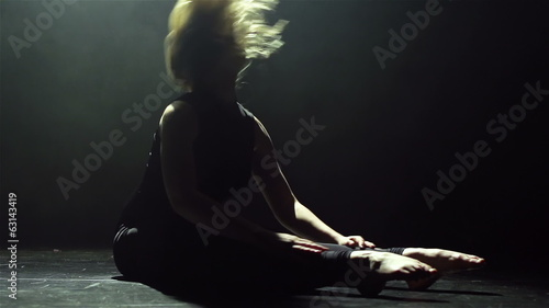 Blond long-haired female performing dance on the floor
