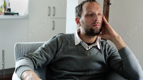 Sad, unhappy young handsome man sitting in armchair at home